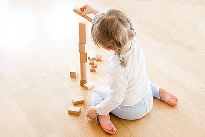 niña sentada en el suelo de espaldas con las piernas en w jugando con tacos de madera