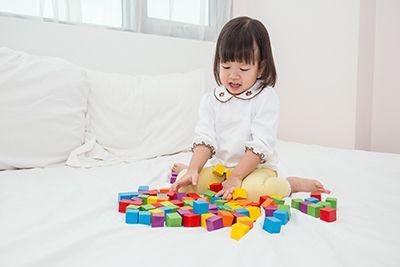 niñas sentada en la cama jugando con piezas de colores