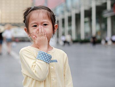 niña tapándose la boca con la mano