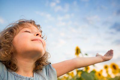 niña con los brazos abiertos respirando aire puro