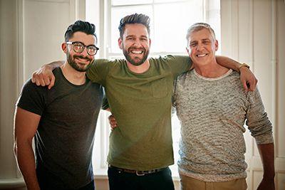 tres hombres abrazados sonriendo