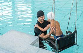 monitor de natación ayudando a niño en piscina
