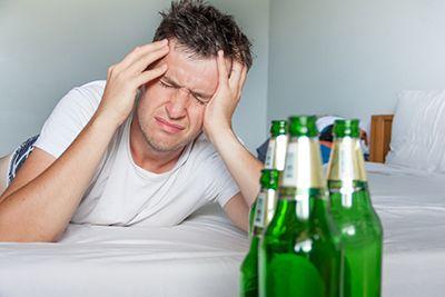 hombre con resaca y unas botellas de cerveza
