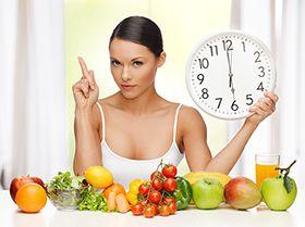 chica con un reloj en la mano y frutas y verduras sobre la mesa