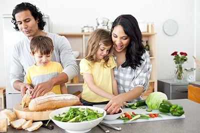 padres con sus hijos preparando una comida vegetariana