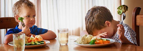 dos niños sentados en la mesa comiendo verduras