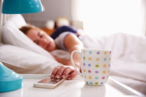 mujer tocando un móvil con la mano y una taza sobre la mesita de noche