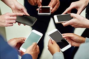 varias manos cogiendo smartphone en forma de estrella