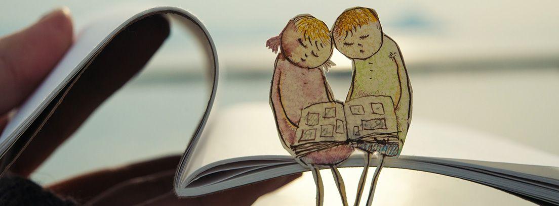 pareja de dibujos sentados encima de un libro