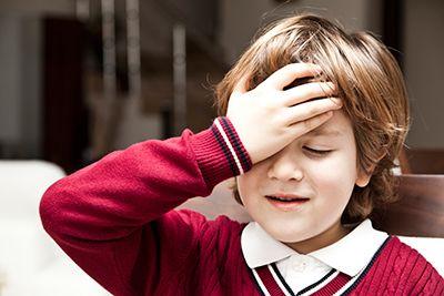 niño con la mano en la frente con gesto de dolor