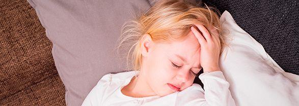 niña tumbada con la mano en la frente