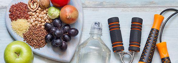 bandeja en forma de corazón con uvas, cerales, legumbres, botella y aparatos para realizar ejercicio