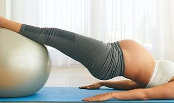 mujer embarazada tumbada con las piernas encima de una pelota