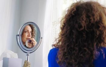 mujer mirándose al espejo con cara de peocupación
