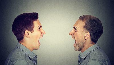 hombre joven y hombre maduro mirándose de frente y gritando