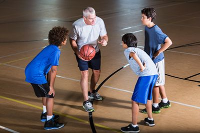 niños con entrenador praticando baloncesto