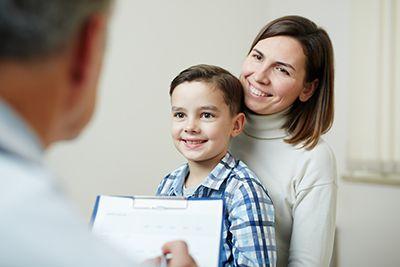 médico asistiendo al niño con su madre