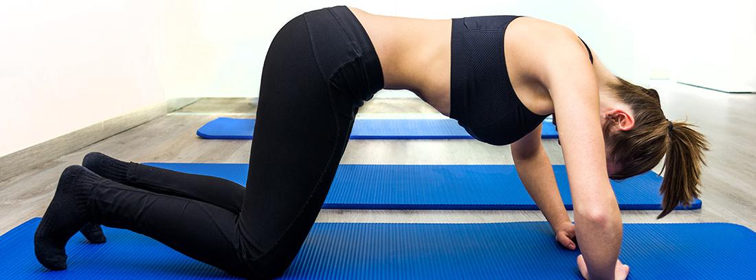 mujer sobre colchoneta realizando ejercicios hipopresivos