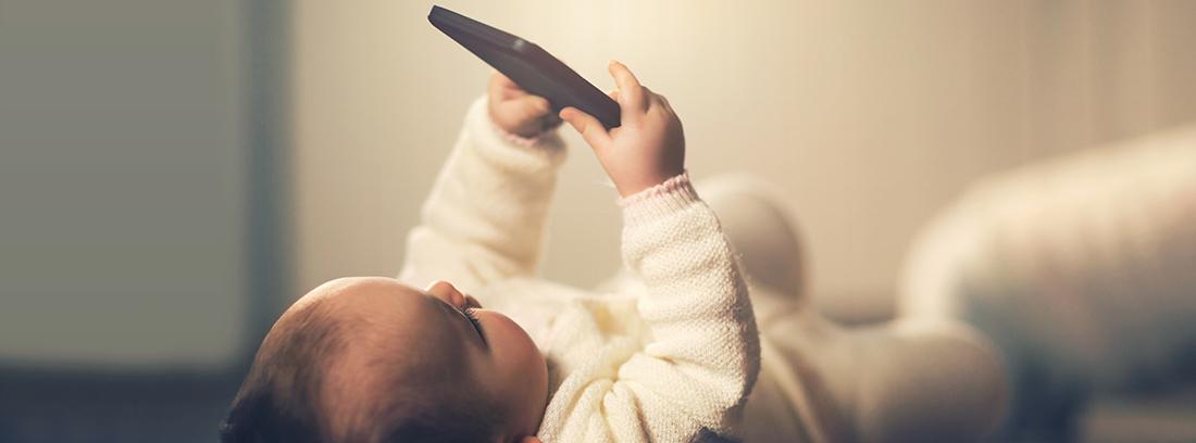 bebé tumbado con un móvil en la mano