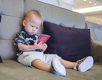 bebé sentado en un sofá con un móvil en las manos