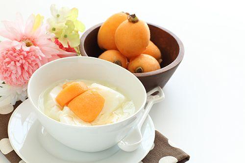 un bol blanco con yogur y trozos de nísperos y otro bol marrón con nísperos y unas flores al lado