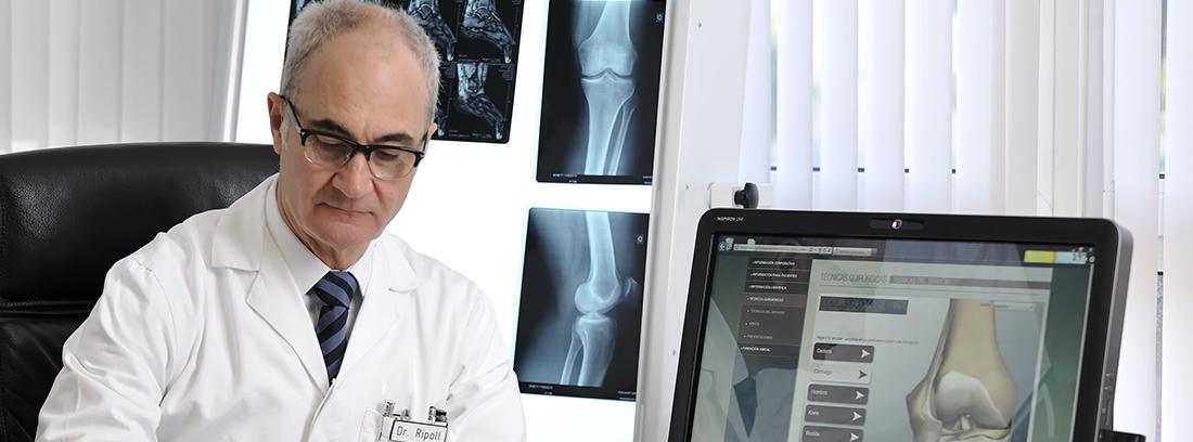 El Doctor Ripoll en su consulta escribiendo un informe en un folio y con el ordenador encendido con la imagen de una rotura de hueso