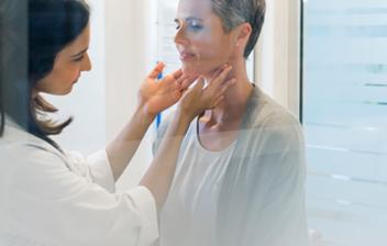 doctora palpando las tiroides a una paciente,titoiditis