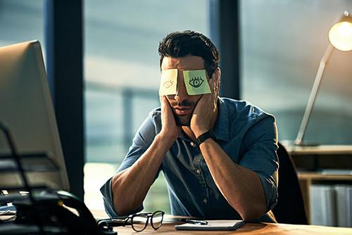 hombre con los codos en la mesa delante de un ordenador con dos po-sit en los ojos