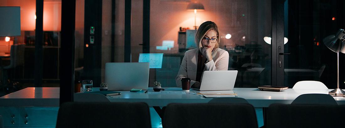 mujer trabajando con un ordenador portátil en la oficina de noche
