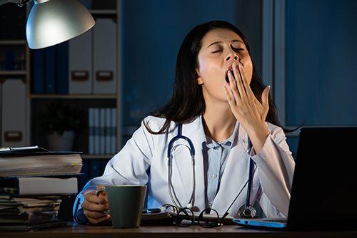 doctora bostezando en el escritorio de un hospital
