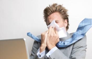 hombre en oficina estornudando