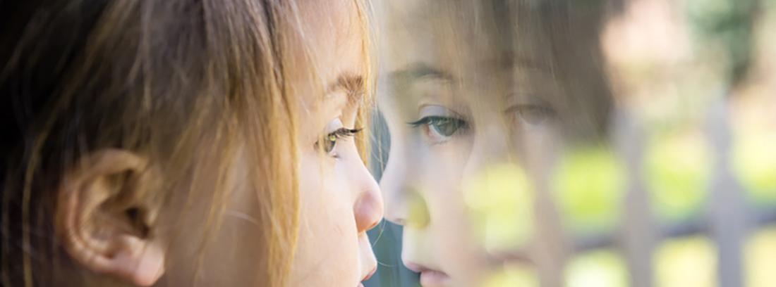 niño reflejado en cristal