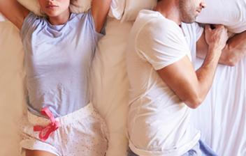 mujer tumbada en la cama y hombre dando la espalda