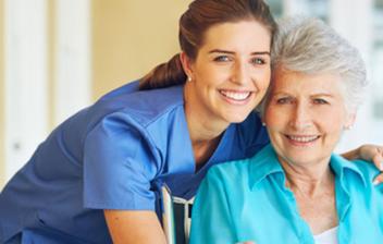 mujer mayor sonriendo con mujer joven sanitaria