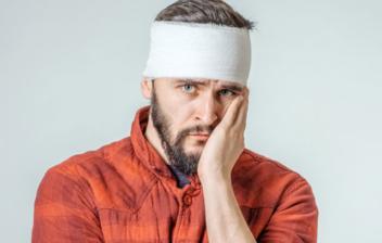 hombre con venda en la cabeza tomándose la cara