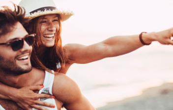 una chica señala subida a espalda de un chico a orillas del mar
