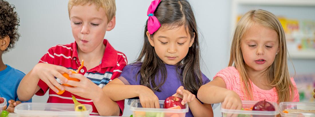 tres niñas tomando alimentos de tuppers
