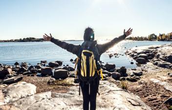 mujer con mochila en la playa