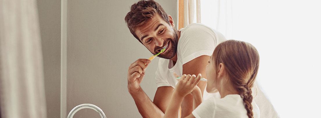 un hombre y una niña cepillándose los dientes