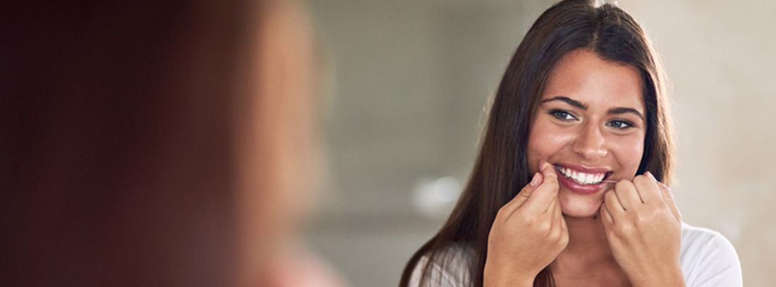 chica limpiándose los dientes con hilo dental