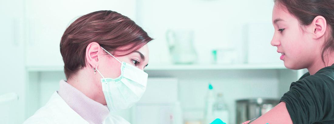 mujer con barbijo vacuna a una niña