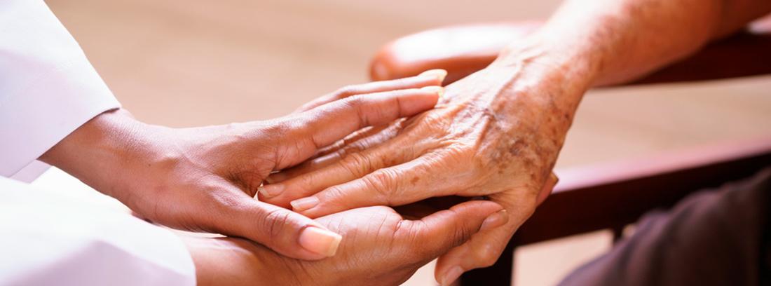 mano de una mujer joven sosteniendo la mano de una persona mayor