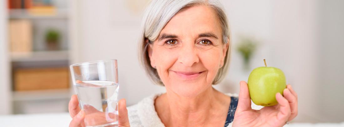 mujer mayor con un vaso de agua y una manzana verde