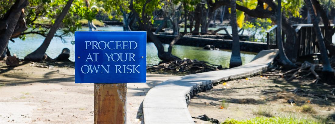camino con un cartel en ingles y un lago de fondo
