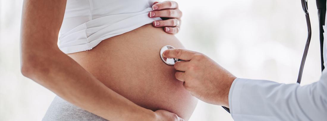 médico escuchando los latidos desde la barriga de una embarazada