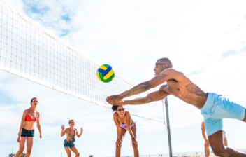 jovenes jugando al voleibol en la playa