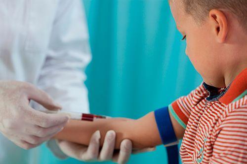 doctor realizando un análisis de sangre a un niño
