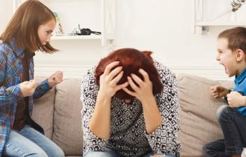 madre sentada en el sofá con las manos en la cabeza, una niña y un niño a cada lado gritando
