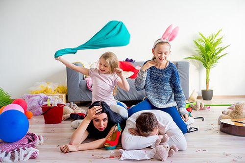padres tumbados en el suelo con las hijas encima de ellos jugando en una habitación con juguetes