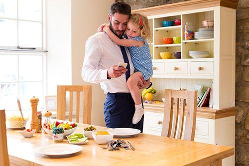padre con su hija en brazos mirando el móvil al lado de una mesa con desayunos